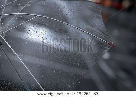 Transparent umbrella with rainy drops close up on street city lights background. 3D illustration