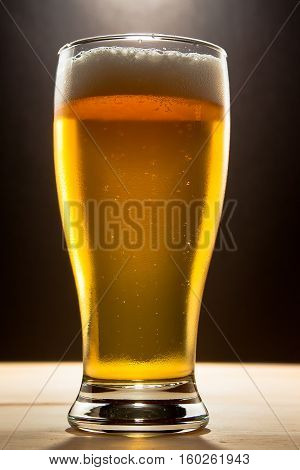 glass of beer shot against a dark background