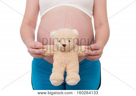 The belly asia pregnant woman holdind a teddy bear doll isolate on white background
