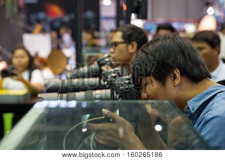 December 2 2016. A man tries out Nikon's newest telephoto lens at a camera exhibition. Bangkok Thailand.