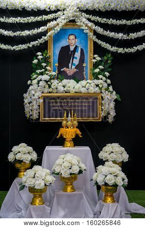 November 29 2016. White flowers decorate the picture of King Bhumibol Adulyadej in the traditional academic dress of Thammasat University Ta Prachan campus. Vertical orientation. Bangkok Thailand.
