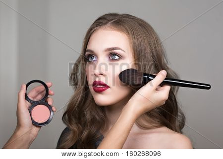 Make-up process, the face of a beautiful young woman and makeup artist's hands with a brush and blush. Cropped imag