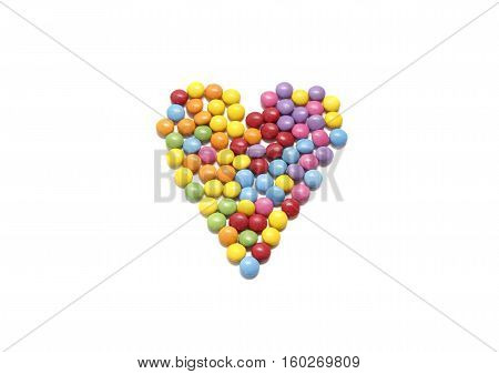Abstract heart from colored chocolate candy in multicolored glaze isolated on white background