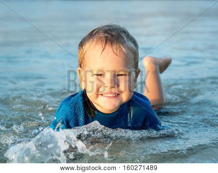 Cute boy plays in a sea