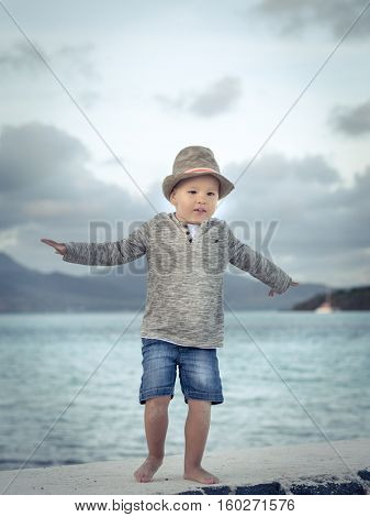Child having fun on the beach at sunset time