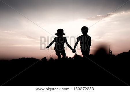 Silhouettes of kids jumping off a hill at sunset. Little boy and girl jump high holding hands. Brother and sister having fun in summer. Friendship freedom concept. Fraternal twins on vacation in mountains.