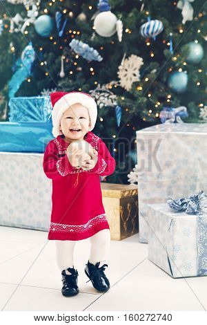 Portrait of happy smiling Caucasian baby girl toddler with blue eyes in red dress and Santa Claus hat standing by New Year tree near gift boxes holding golden ornament decoration lifestyle image.