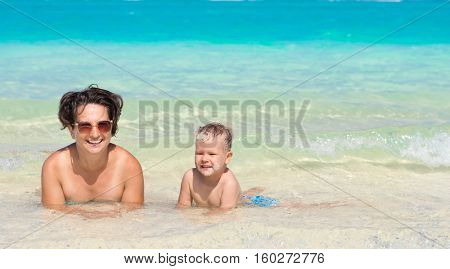 Mother and son relaxing in the sea. Mauritius. Panorama