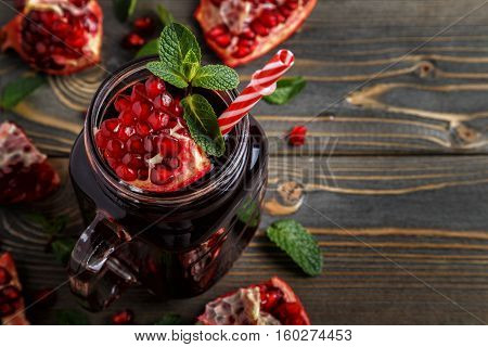Glass of pomegranate juice with fresh pomegranate fruits and mint on wooden table healthy drink concept.
