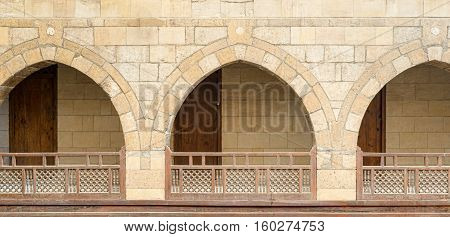Front view of three arches with interleaved wooden balustrades at the arcade surrounding the courtyard of caravanserai (Wikala) of al-Ghuri Medieval Cairo Egypt