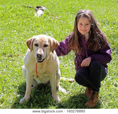 nice little girl with labrador dog on the meadow