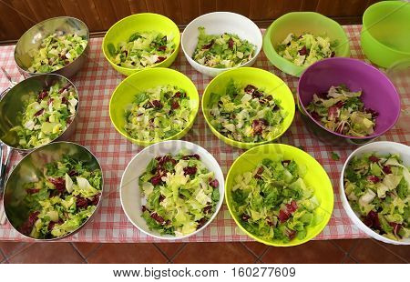 table with many bowls of lettuce and salad in the company lunchroom