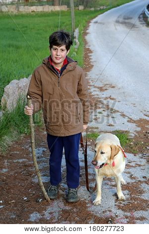 worried boy walks with his dog on a leash in the trail in the mountains