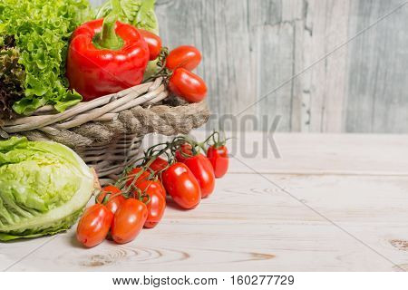 Ingredients for fresh spring healthy green salad- green and red frech lettuce salad leaves paprika tomatoes - healthy low calorie food