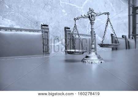 Decorative Scales of Justice on the table in courtroom BLUE TONE