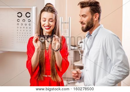 Female patient wearing try-on tool for vision check with ophthalmologist in front of the eye chart in the cabinet. Eye doctor with patient in the clinic