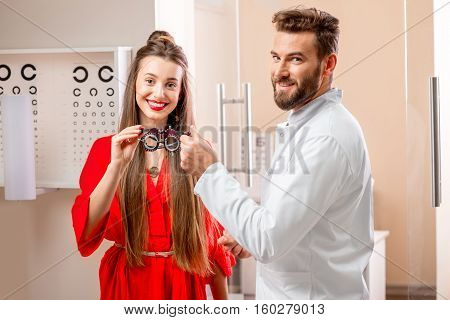 Ophthalmologist giving try-on tool for vision check to the young female patient in front of the eye chart in the cabinet. Eye doctor with patient in the clinic