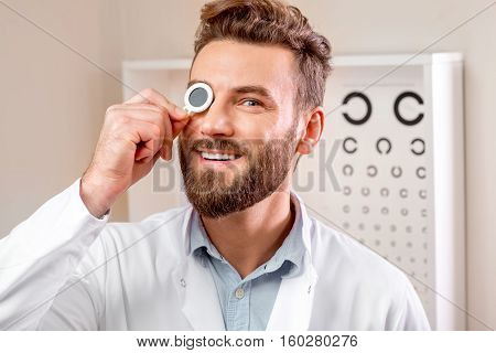 Close-up portrait of handsome smiling ophthalmologist in front of the eye chart in the cabinet