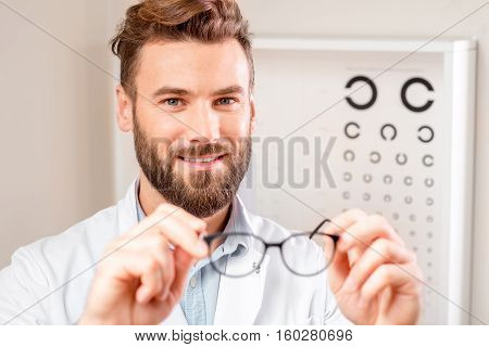 Handsome ophthalmologist looking at the glasses in front of the eye chart in the cabinet.
