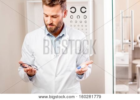 Eye doctor choosing between eyeglasses and lenses standing in front of the eye chart in the cabinet
