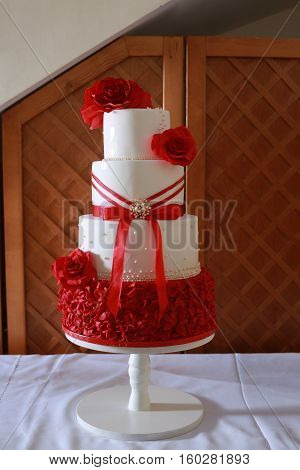 4 layer white wedding cake decorated with red edible marzipan flowers and red satin ribbon placed on a white round stand