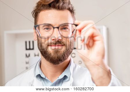 Handsome ophthalmologist looking through the glasses on the eye chart background in the cabinet