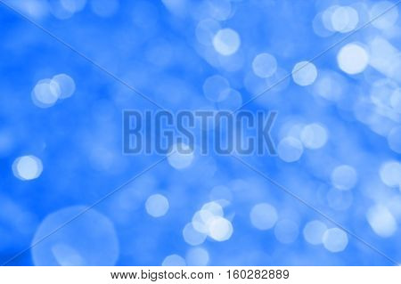 Abstract dark blue background with white bokeh and patches of light