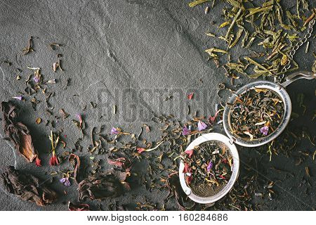 Different tea leave and strainer on the dark stone table top view