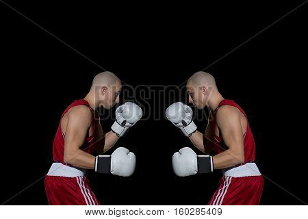 identical young adult male boxers standing against each other wearing white boxer gloves, red clothes, black background, prepared for punch