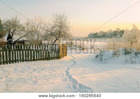 Winter landscape - winter scene with house and wooden fence among  nature at sunset. Landscape rural scene in cold frosty trees and winter nature at sunset. Landscape rural winter scene in cold winter weather under soft evening sunlight