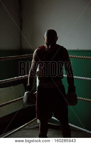 portrait of male boxer standing in the corner of the ring, backlit, silhouette