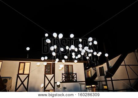 Wedding balloons with light inside on air at night wedding ceremony.