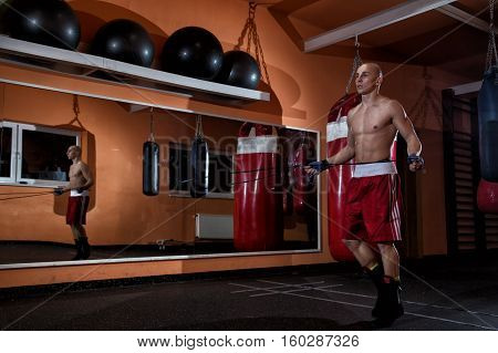 young male adult athlete jumping through a rope in a gym with big mirror