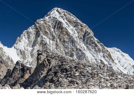 Trekkers Coming Up To Kala Patthar - The Everest Mount View Point - With Pumori Mountain On The Back