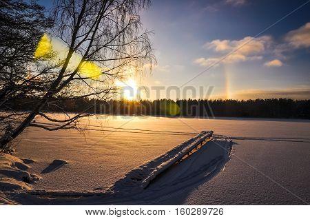 Fishing bridge on background of sun halo, sunset, and snowed lake in winter.