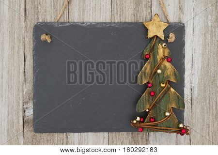 Old fashion Christmas hanging chalkboard background A retro chalkboard with a rustic primitive Christmas tree hanging on weathered wood background with copy space for your message