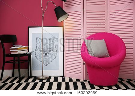 Pink armchair in stylish interior
