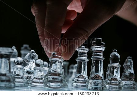 Close-up view on the transparent glass chess board with male hand holding one of the chess pieces. Black background.