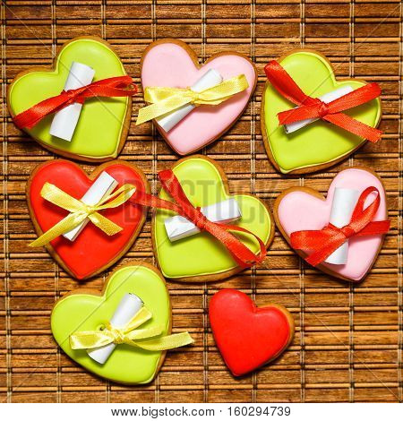 Colorful gingerbread cookies tied with ribbons with pieces of paper with wishes on gunny background