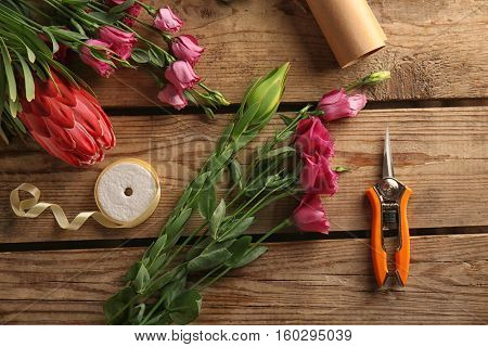 Beautiful flowers and florist equipment on wooden background
