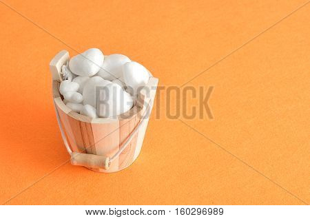 Valentines day. A wooden bucket filled with polystyrene hearts isolated against an orange background