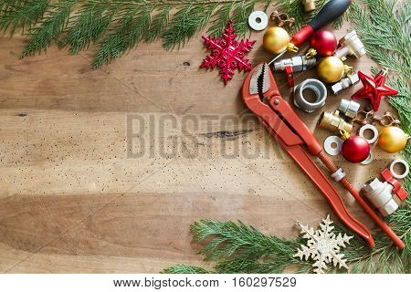 Plumber  Tools, Fittings And Christmas Decorations On Wooden Background