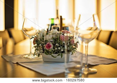 Simple wedding flower center piece arranged in the middle of the table on white cloth surrounded by clean, empty wine glasses, photo taken indoors, in restaurant. Background are huge windows, golden hour tones