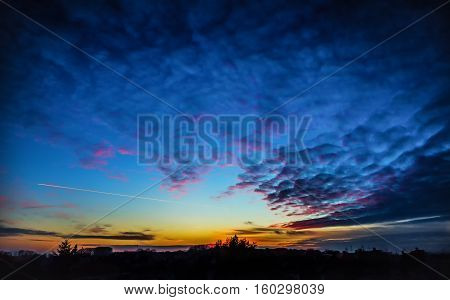 Sunset sky panorama with airplane silhouette of trees and village houses.