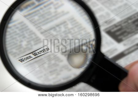 Searching for a job through the newspaper sections with a magnified glass.