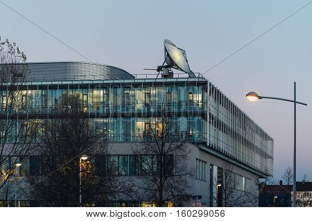 BIg communication satellite antenna on the roof of a media news corporation office building at dusk