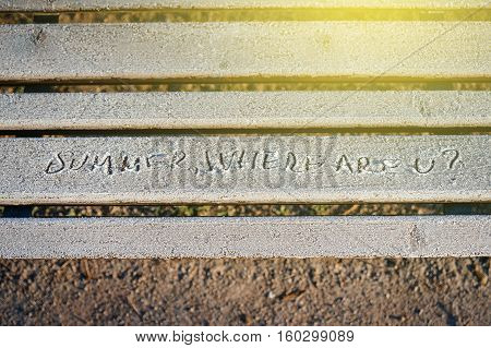 Summer where are u? inscription on park bench covered with snow early in the morning