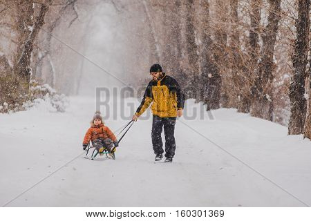 Father and son with a sledge outdoor in the snow snowing
