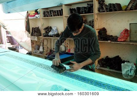JAIPUR, INDIA - FEBRUARY 16: Craftsman decorating fabric with traditional wood blocks Silk Road Bazaar near Jaipur, Rajasthan, India on February 16, 2016.