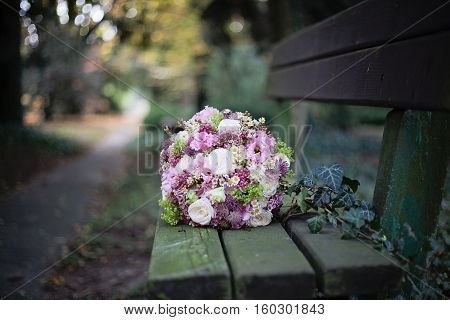 medium sized pink rose and wild flower wedding bouquet on the bench covered with moss taken in the park daytime autumn